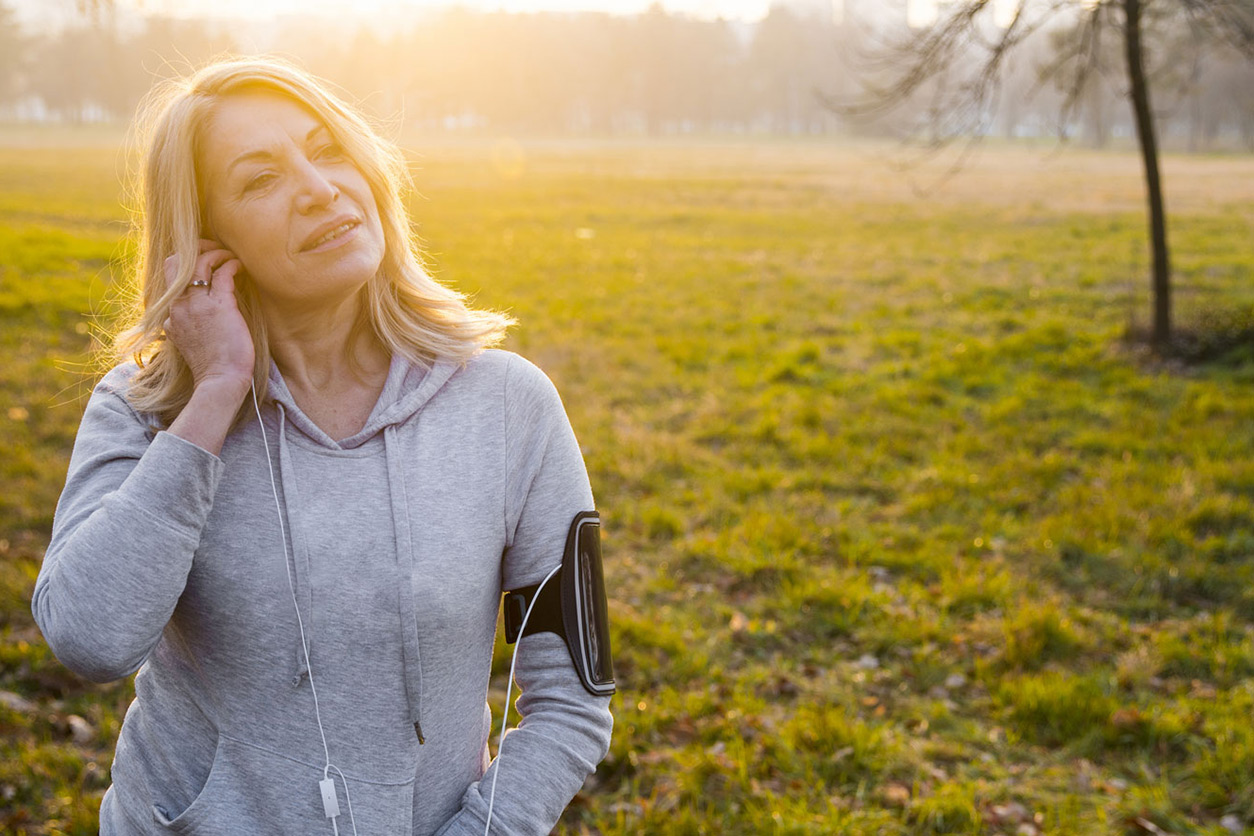 Woman standing in field listening to music
