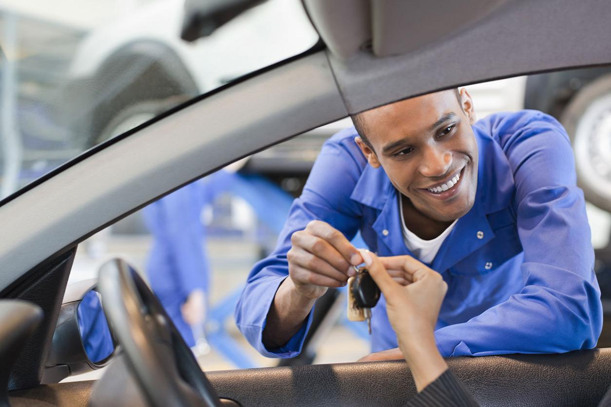 Man handing keys through car window to driver