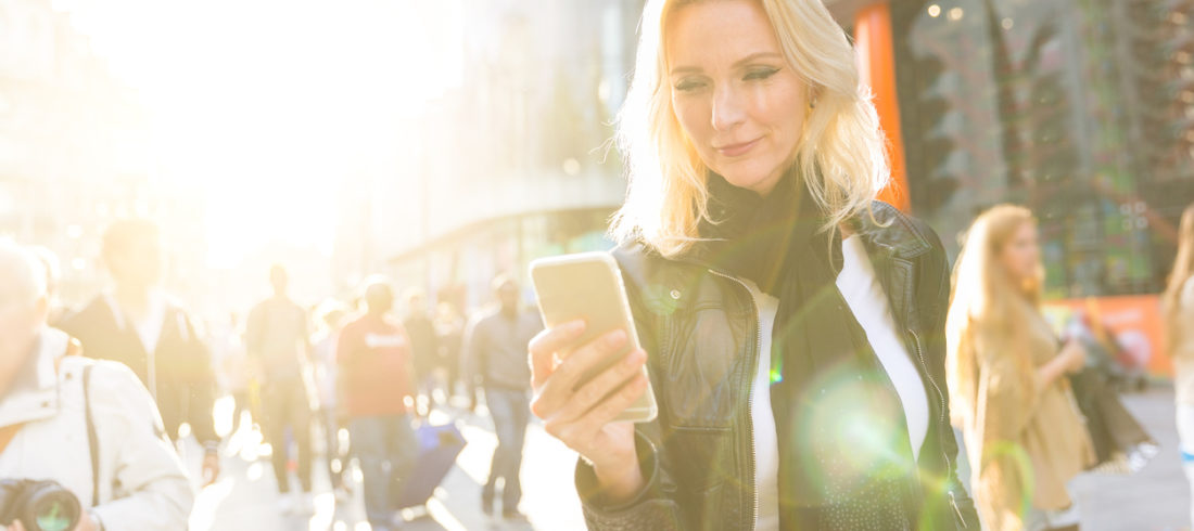 Blonde woman looking at smart phone in London