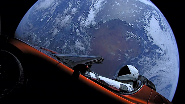 An astronaut drives a red sports car through outer space in front of the earth.
