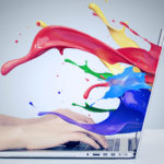business woman's hands on keyboard using laptop with colorful splashes, liquid effect out of monitor screen computer display