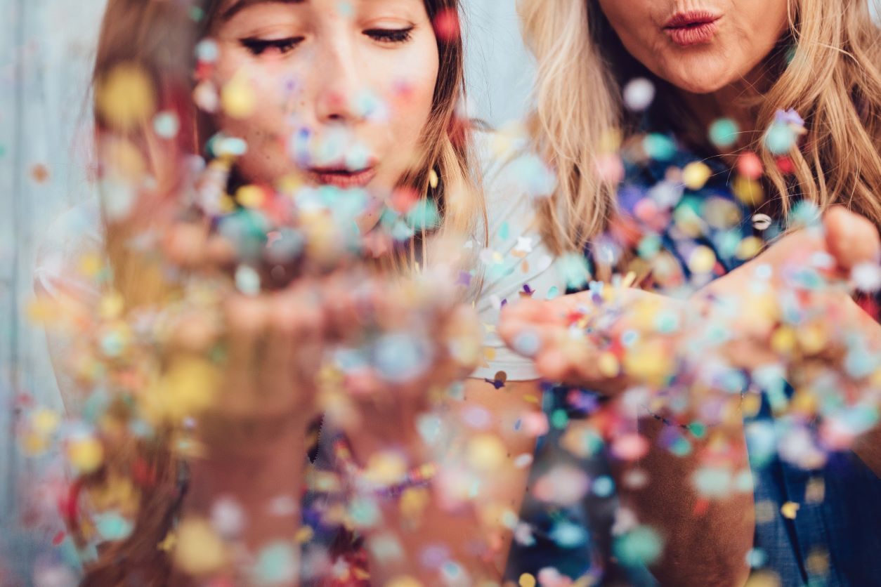 Two ladies blowing confetti