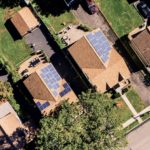 Ariel photograph of neighbhor hood roofs with solar panels