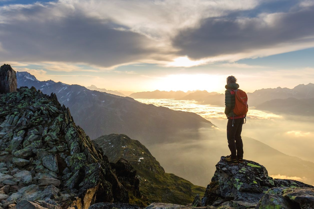 Man standing on a mountain top looking out at a sunrise